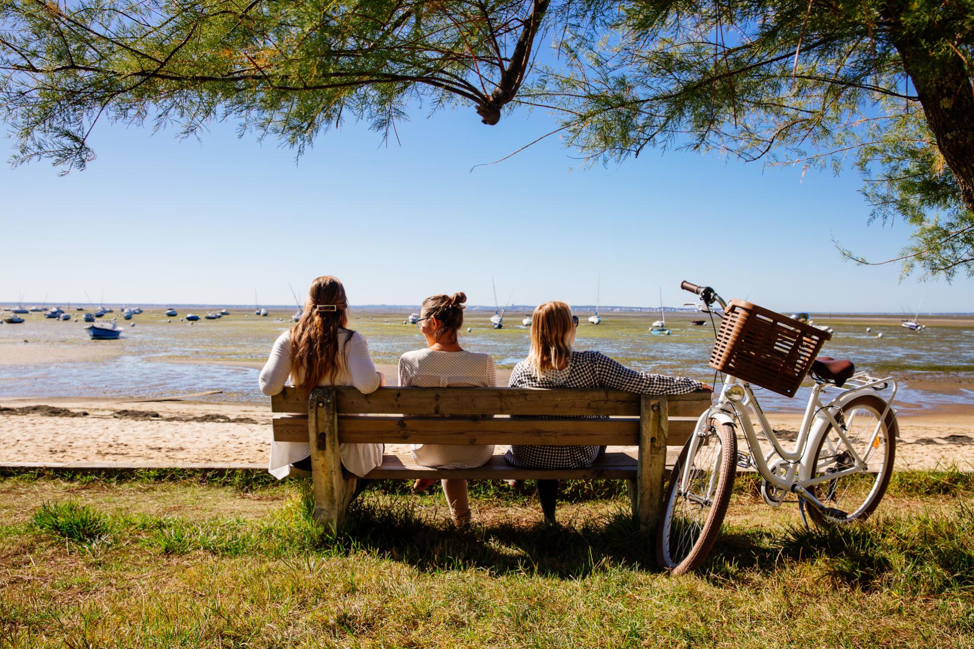 Andernos les bains à vélo assis sur un banc face au Bassin d'Arcachon crédit photo Agence les Conteurs