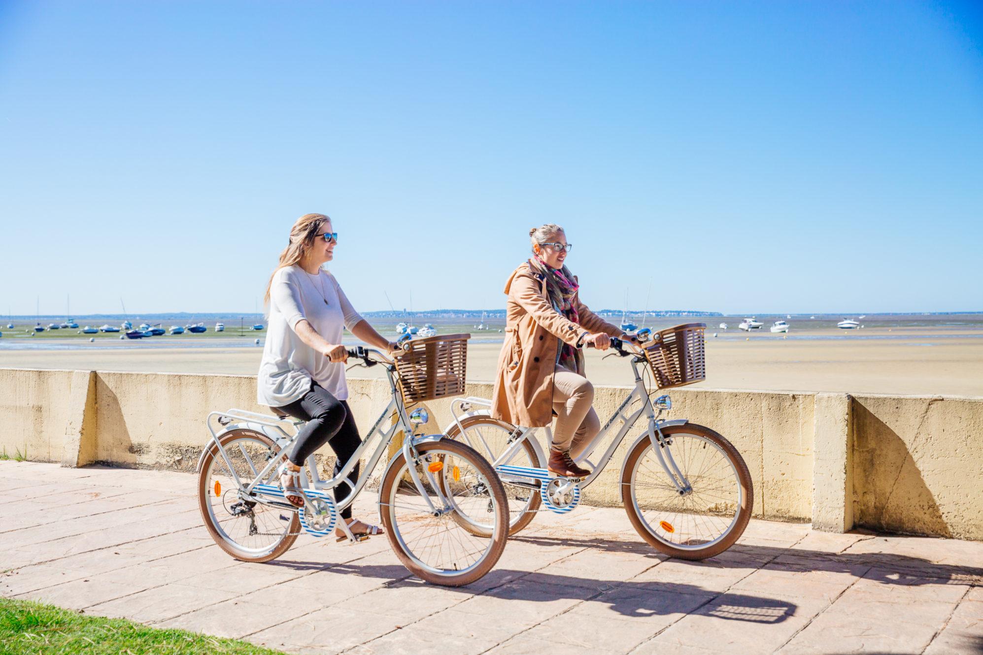Deux personnes à vélo au bord de l'eau à Andernos